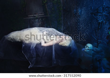 Sleeping Beauty. Beautiful lifeless bride in white dress lying on the shore in a tomb. Dark mystery scene. Low key