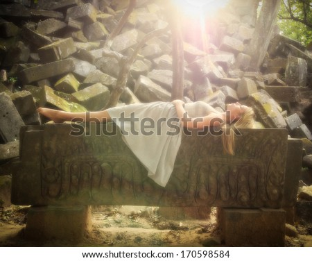Sleeping Beauty fairytale princess lying down on a stone altar in the forest. - stock photo