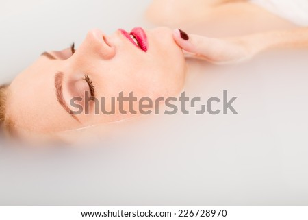 sleeping beauty in spa: closeup portrait of sexy elegant pinup girl with silk skin having fun happy relaxing lying in milk water on copy space background - stock photo