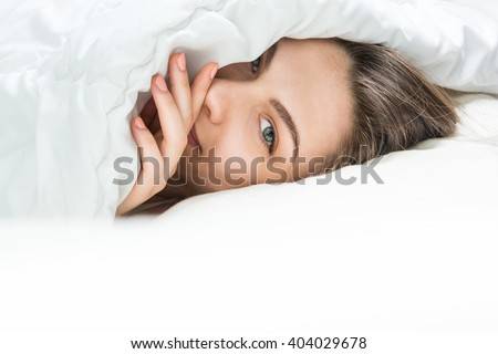 Sleeping Beauty looking out of under the blanket. Sweet dreams in the tender soft bed. Beautiful female eye in a whisper tells secrets. Good morning (night) or sweet dreams