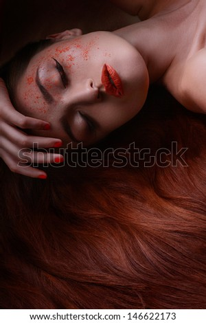 Sleeping beauty. Portrait of beautiful women lying with her hand in hair and face pouring with red powder