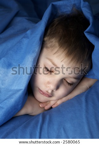 sleeping boy in blue bedclothes