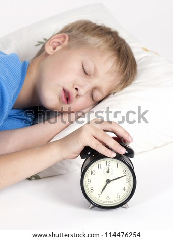 Sleeping boy with alarm clock in front