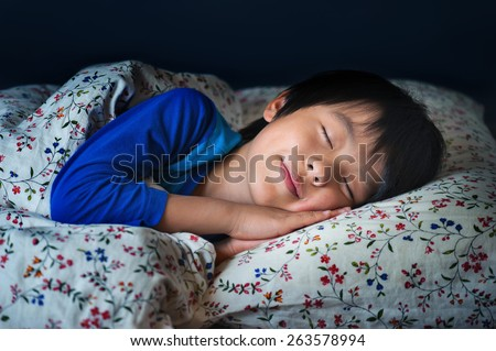 Sleeping boy with happy smile - stock photo