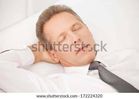 Sleeping businessman. Tired grey hair man in shirt and tie lying on bed and keeping eyes closed - stock photo
