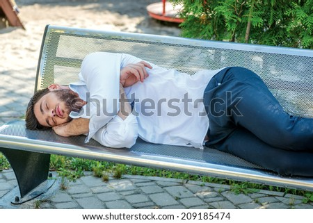 Sleeping businessman. Young businessman sleeping on a bench after a hard day - stock photo