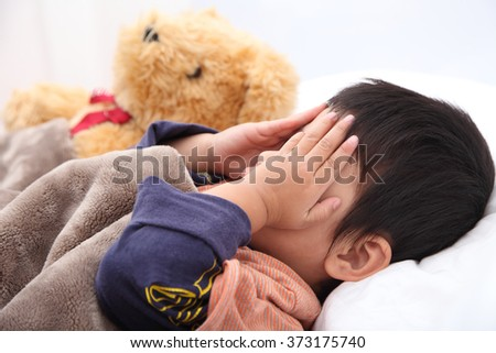 Sleeping child hands off covering face on the bed.