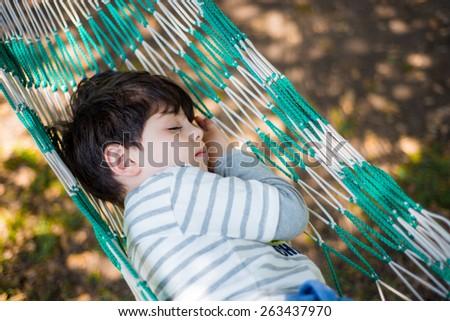 Sleeping child in hammock - stock photo