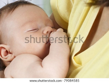 Sleeping child in the arms of Mom - stock photo