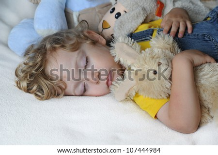 Sleeping child with toys - stock photo