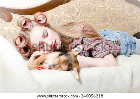 Sleeping cute dog and blond beautiful pinup girl with red lips curlers in her hair lying in bed  - stock photo