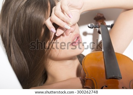 Sleeping cute sensual young musician girl with brunette hair with raised hand holding brown wooden string musical instrument of violin lying on white background, horizontal picture - stock photo