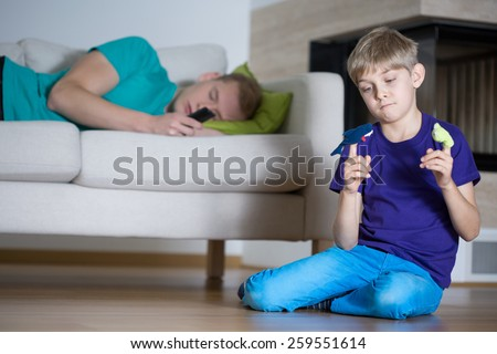 Sleeping father and little sad boy playing alone - stock photo