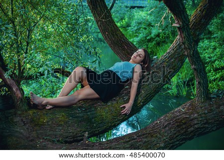 Sleeping girl lying on the trunk of the tree