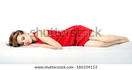 Sleeping girl on a leather sofa isolated on white background