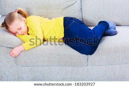 Sleeping girl on sofa. Tired child relax.