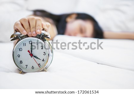 Sleeping girl with her hand touching alarm clock on bed - stock photo