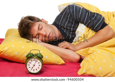 Sleeping handsome young man with alarm clock - stock photo