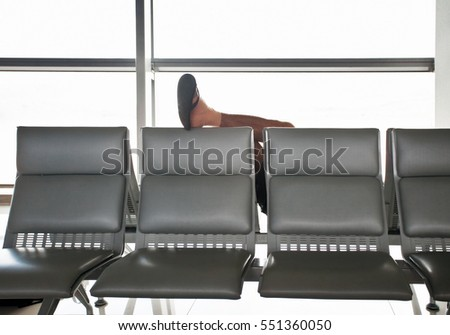Sleeping in the airport man put his foot on the seat back