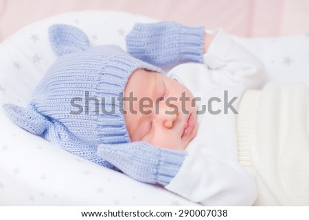 Sleeping little baby wearing knitted blue hat with ears and mittens lying in beautiful cradle. Security and childcare concept