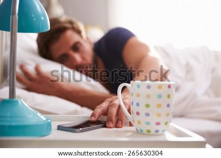 Sleeping Man Being Woken By Mobile Phone In Bedroom - stock photo