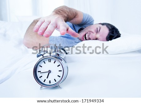 sleeping man disturbed by alarm clock early morning  - stock photo