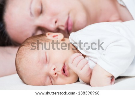 sleeping mother and her cute baby - stock photo