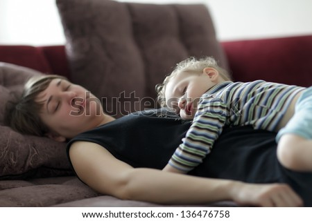 Sleeping mother and toddler on a sofa at home - stock photo