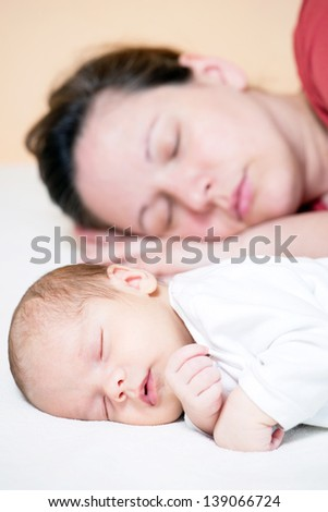 sleeping mother with her baby - stock photo
