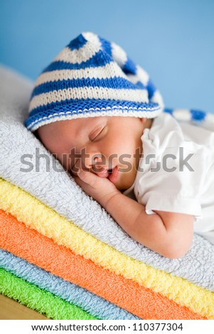 Sleeping newborn baby closeup portrait on colorful towels stack - stock photo