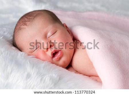 Sleeping newborn baby girl on tummy - stock photo