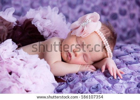 Sleeping newborn baby girl with pink flower headband lying on purple blanket. - stock photo