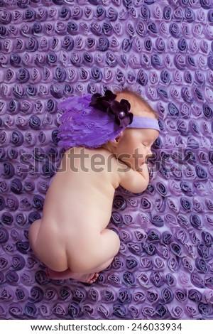 Sleeping newborn baby girl with pink flower headband lying on purple blanket. - stock photo