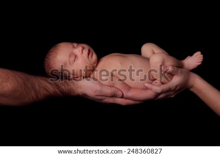 Sleeping newborn baby in her arms mom and dad. Concept of love, protection of children. Studio, black background