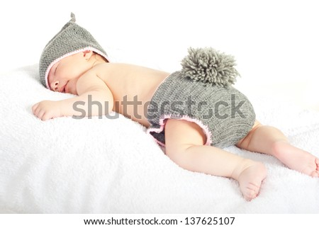 Sleeping newborn baby in knitted bunny costume isolated on white background