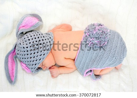 Sleeping newborn baby in rabbit costume on a knitted blanket