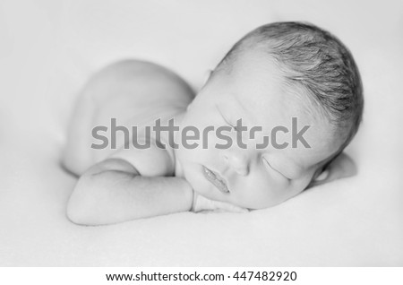 sleeping newborn baby on a blanket. close up portrait. black and white - stock photo