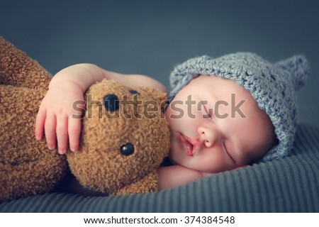 sleeping newborn baby on a blanket with a teddy - stock photo
