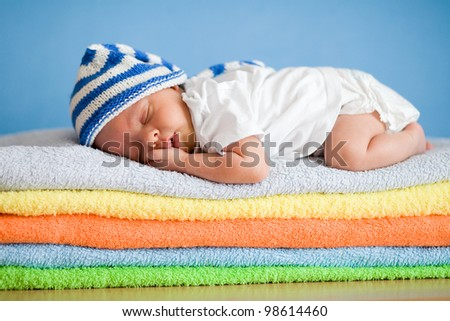 Sleeping newborn baby on colorful towels stack