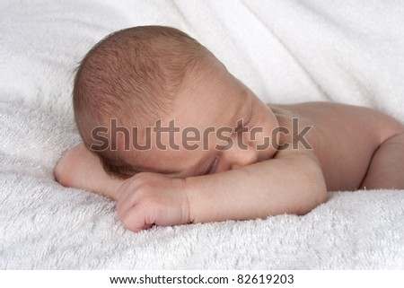 sleeping newborn baby resting head on arms - stock photo