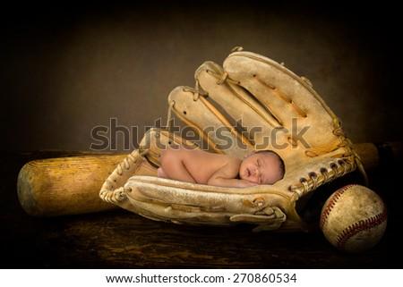 Sleeping newborn baby sleeping in an old baseball glove - stock photo