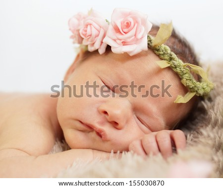 Sleeping newborn baby with pink rose garland around head - stock photo