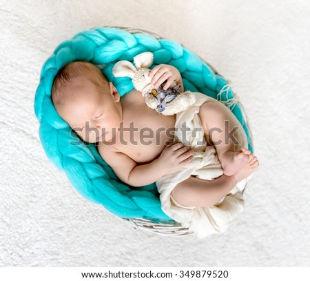 Sleeping newborn boy with hare on a turquoise plaid - stock photo