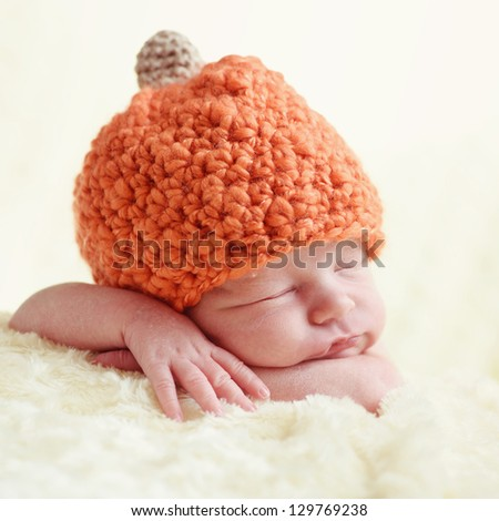 sleeping newborn wearing pumpkin hat - stock photo