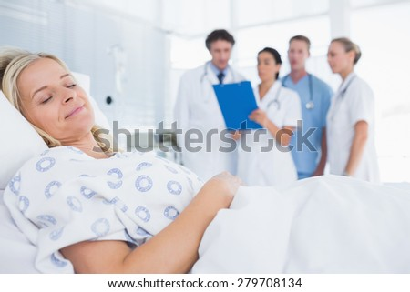 Sleeping patient with doctors behind in hospital room - stock photo