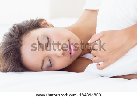 Sleeping pretty brunette lying on bed hugging pillow at home in the bedroom