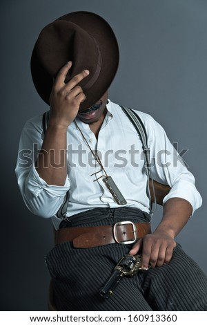 Sleeping retro afro america western cowboy man with mustache. Sitting in wooden chair. Holding gun. Wearing brown hat. Cool tough guy. - stock photo