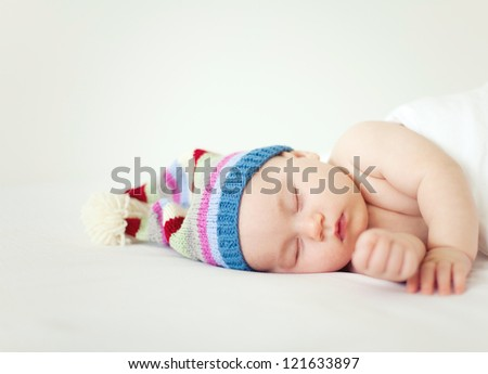 sleeping sweet baby wearing funny striped hat