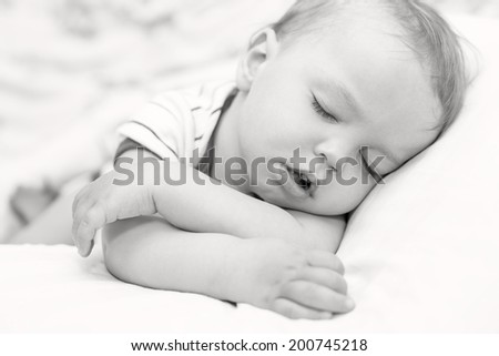 sleeping  toddler baby boy on a white background (black and white) - stock photo
