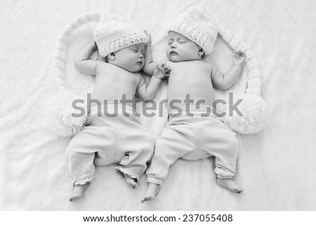 sleeping twins wearing funny hats with big pompoms - stock photo